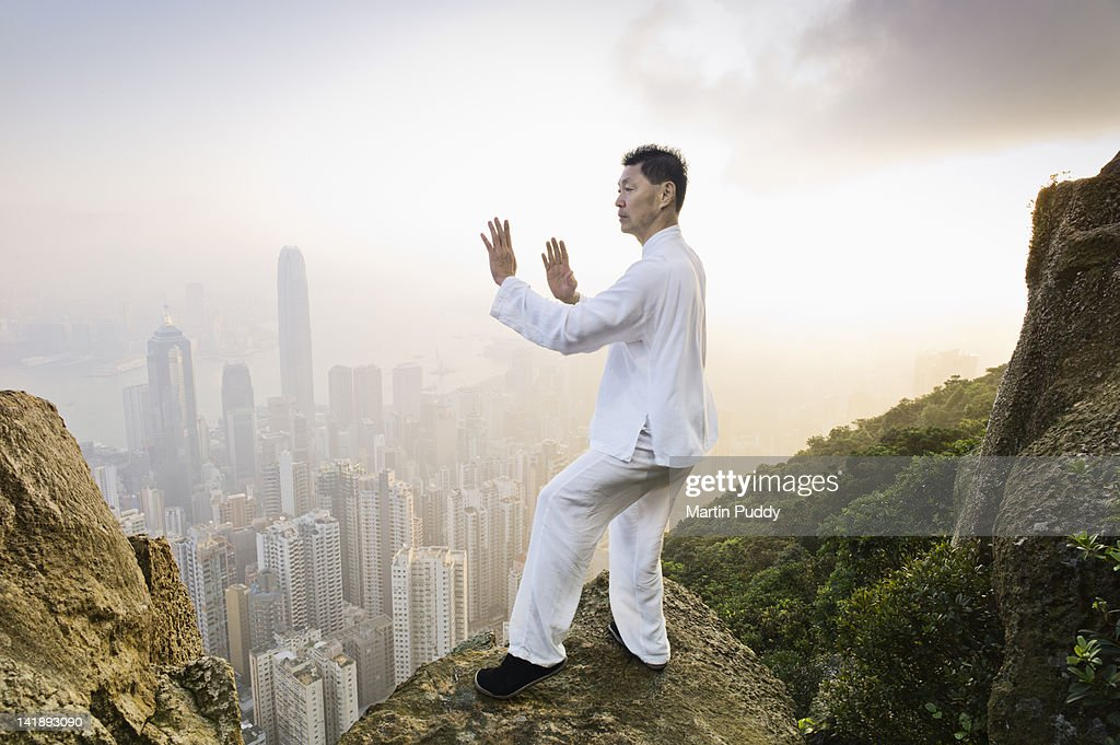 Man practicing Tai Chi infront of skyline : Photo
