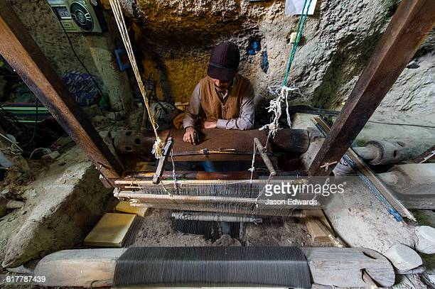 A man practicing traditional cloak weaving on an antique loom in a cave in the desert.
