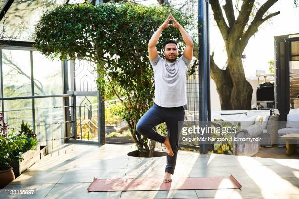 man practicing tree pose in yoga class - tree position stock photos and pictures