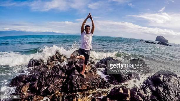 Man Practicing Tree Pose On Rocky Shore Against Sky