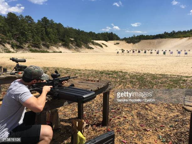 man practicing with rifle at shooting range - sportschießen stock-fotos und bilder