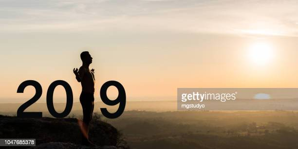 man  practicing yoga during the celebration new year 2019 - 2019 foto e immagini stock