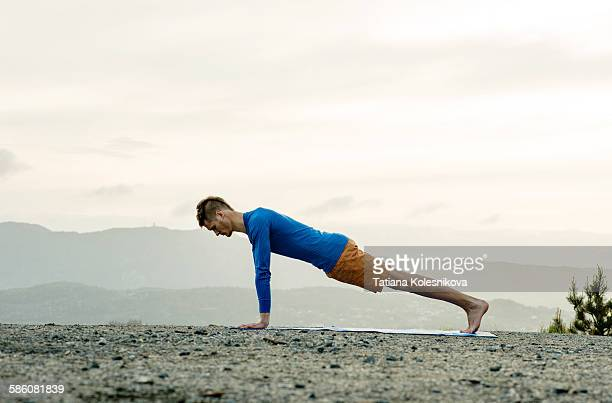 Man practicing yoga in the mountains