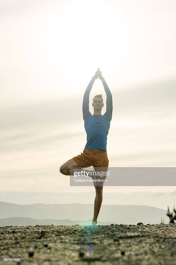 Man practicing yoga in the mountains : Stock Photo