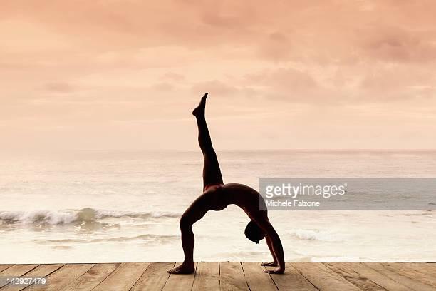 Man practicing yoga on a beach, India