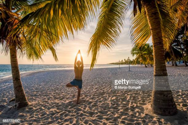 Man practicing yoga on a tropical beach at sunset. Saona Island, Dominican Republic.