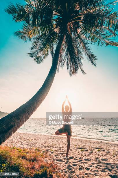 man practicing yoga on the beach - self improvement stock pictures, royalty-free photos & images