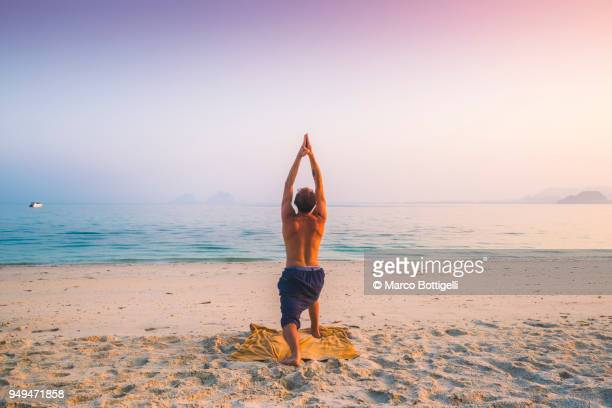 Man practicing yoga on the beach