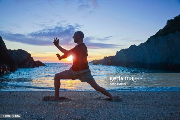 man practising shaolin kung fu at sunset - martial arts stock pictures, royalty-free photos & images