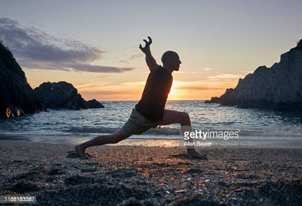 man practising shaolin kung fu tiger stance in woolacombe, devon - kung fu yoga stock pictures, royalty-free photos & images