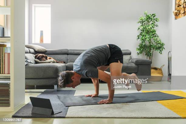 man practising yoga at home - yoga stock pictures, royalty-free photos & images