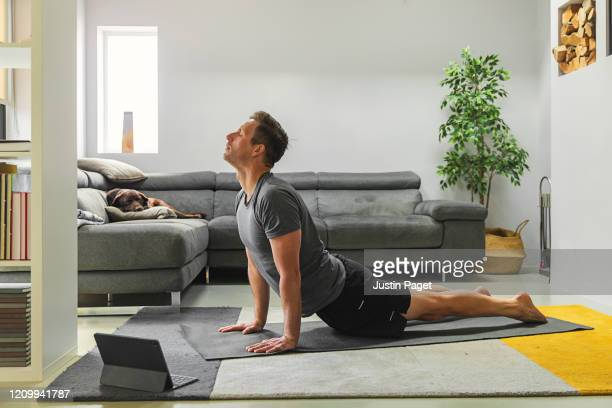 man practising yoga at home - exercising stock pictures, royalty-free photos & images