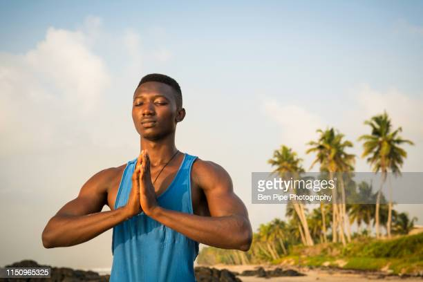 man practising yoga on beach - ghana independence stock pictures, royalty-free photos & images