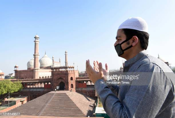 Man praying at home opposite the Jama Masjid on the occasion of Eid-ul-Fitr during lockdown against coronavirus on May 25, 2020 in New Delhi, India.