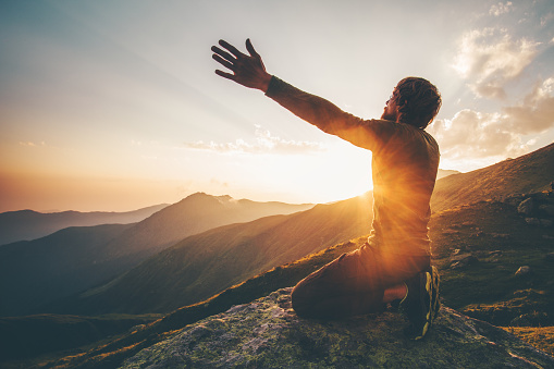 Man praying at sunset mountains raised hands Travel Lifestyle spiritual relaxation emotional concept vacations outdoor harmony with nature landscape 1028901502