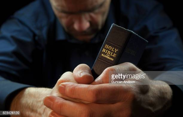 a man praying holding a holy bible - bible stock pictures, royalty-free photos & images