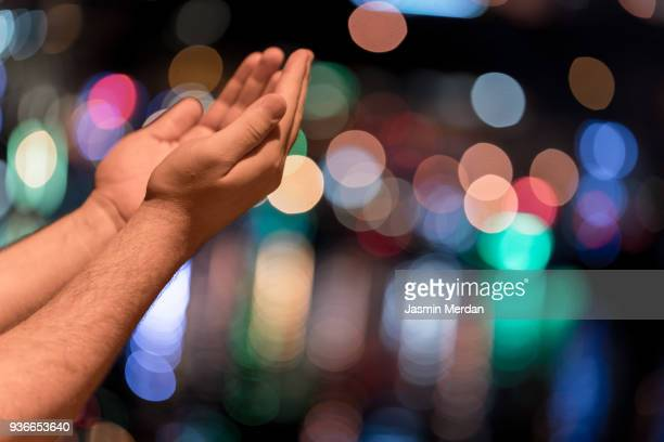 man praying in city at night - jasmin lord stock-fotos und bilder