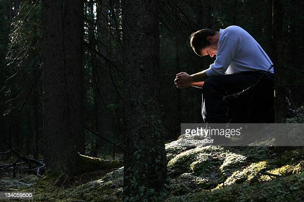 Man Praying in the Forest