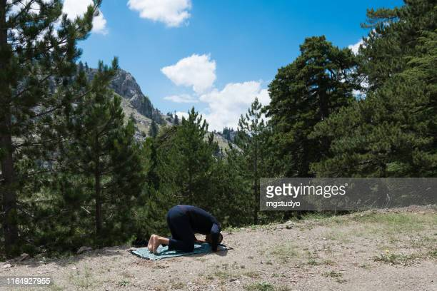 man praying outdoors in nature - allah stock pictures, royalty-free photos & images