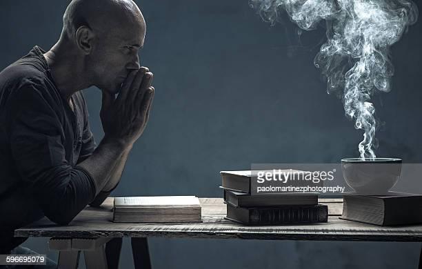 Man praying sitting at table