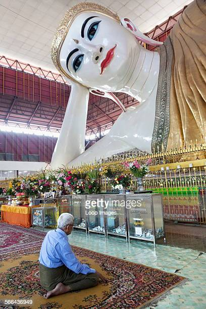A man praying to the reclining Buddha at Chauk Htat Gyi in Yangon in Myanmar