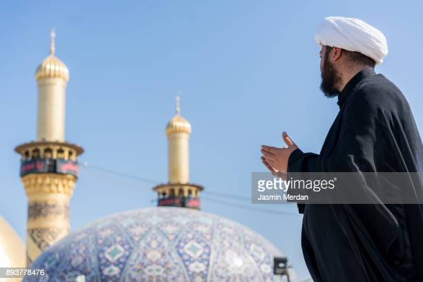 Man praying with mosque on background