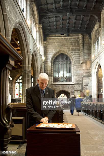 A man prays after having lit a candle in memory of murdered aid worker Alan Henning in Eccles Parish Church in Eccles north west England on October 5...