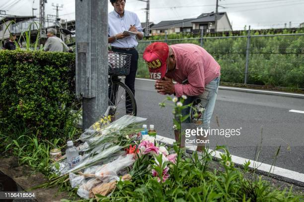 Man prays after laying flowers near the Kyoto Animation Co studio building following an arson attack on July 19, 2019 in Kyoto, Japan. Thirty three...