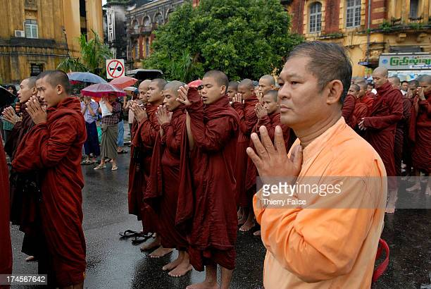 A man prays alongside Burmese Buddhist monks gathered near the Sule pagoda one of the most popular in Rangoon to protest against the military junta