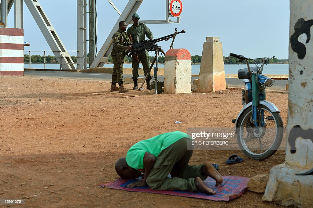 A man prays as Malian soldiers man the entrance to a strategic bridge on the Niger river on January 22, 2013 near Markala, 270 kms north of Bamako. Mali's army chief said on January 22 that his French-backed forces could reclaim the northern towns of Gao and fabled Timbuktu from Islamists in a month, as more offers of aid poured in for the offensive. French planes bombed a major base of the Al-Qaeda in Islamic Maghreb (AQIM) near Timbuktu as local sources said a mansion belonging to Libyan former strongman Moamer Kadhafi was destroyed.