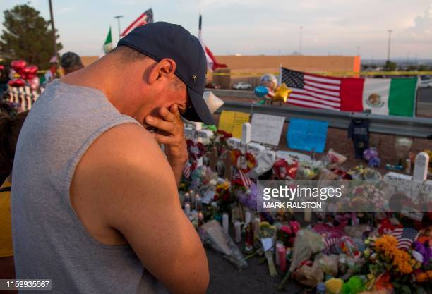 A man prays at a makeshift memorial for victims of Walmart shooting that left a total of 22 people dead at the Cielo Vista Mall WalMart in El Paso...