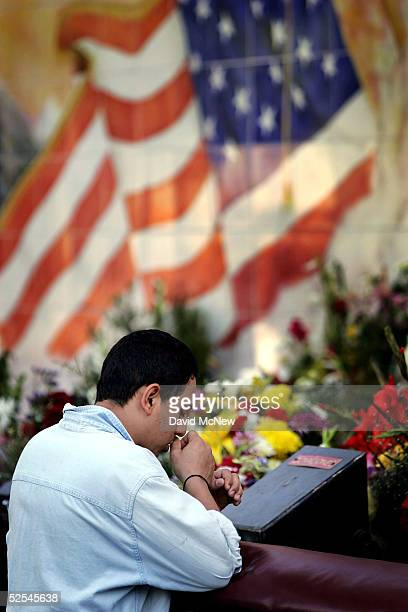 A man prays at an alter near a mural with an American flag outside the Iglesia de la Placita at Nuestra Senora Reina de Los Angeles or Our Lady Queen...
