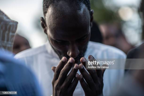 A man prays at the burial of Abdalla Mohamed Dahir and Feisal Ahmed on January 16 2018 in Nairobi Kenya The two men who worked together were killed...