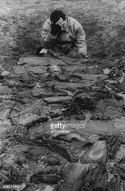 A man prays at the edge of the stone memorial resembling the cremation pit at the Treblinka extermination camp Poland 1994
