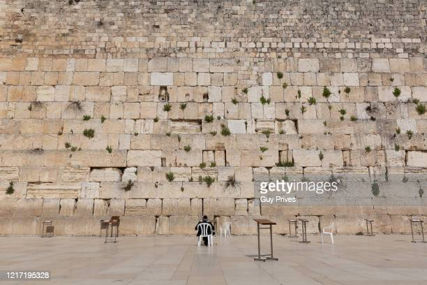 A man prays at the empty Western Wall in the old city during a government enforced lockdown due to the coronavirus on April 06 2020 in Jerusalem...
