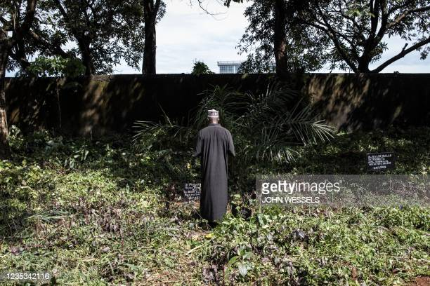 Man prays at the famous Bambeto Cemetery in Conakry on September 18 as the Bambeto cemetery is where most opposition supporters who lost their lives...