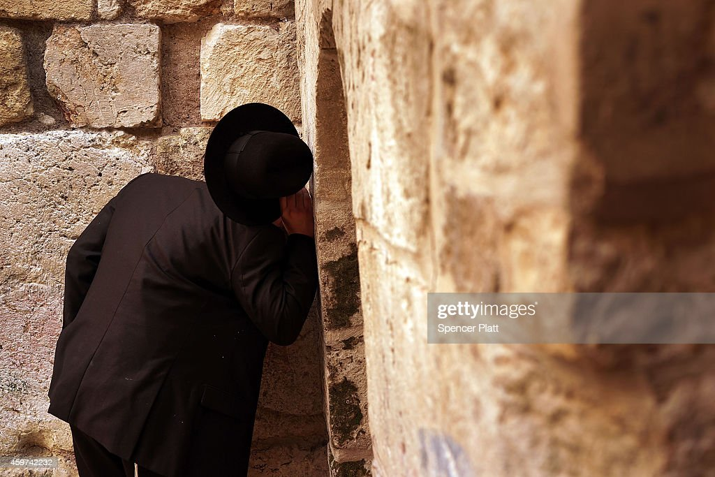 A man prays at the Little Western Wall, also known as HaKotel HaKatan, on November 30, 2014 in Jerusalem, Israel. Nine Israelis have been killed in a series of stabbings, shootings and hit-and-run attacks in Jerusalem over the past month, unsettling the ancient city of Jerusalem where Jews, Christians and Muslims have lived side by side for thousands of years. The tension and violence on the streets of the city is threatening to further isolate communities and encourage extremist politicians to exploit the situation.