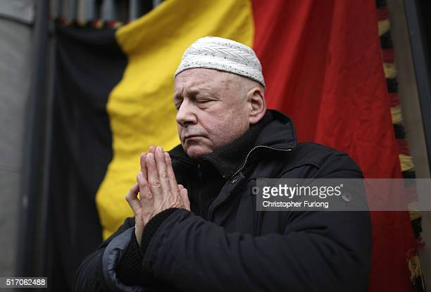 A man prays at the Place De La Bourse in honour of the victims of yesterday's terror attacks on March 23 2016 in Brussels Belgium Belgium is...