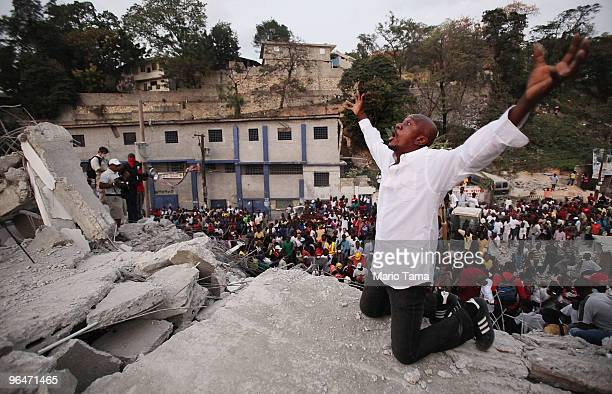 Man prays atop the ruins of St. Gerard University as a large crowd gathers after reports of a person still alive under the rubble February 6, 2010 in...