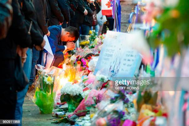 A man prays during a candle light vigil on April 24 2018 in Toronto Canada near the site of a deadly street van attack A van driver who ran over 10...