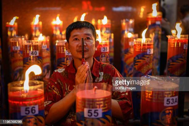 A man prays during the celebration at Xian Ma Temple in Makassar Hundreds of candles are lit at midnight and Prayers for the Chinese Lunar New Year...
