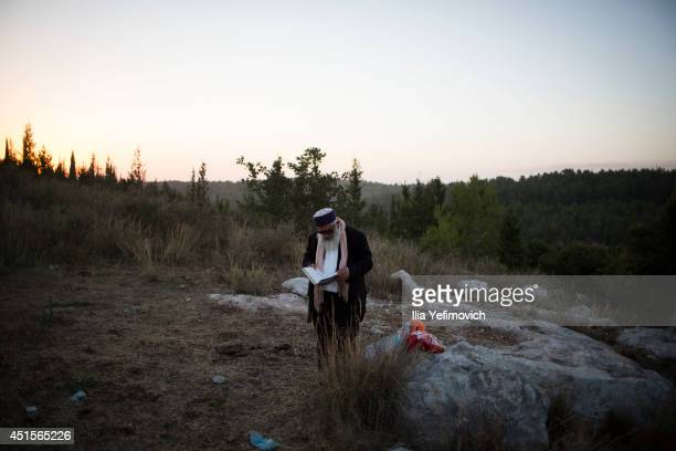 A man prays during the funeral ceremony held for the three Israeli teenagers found dead on July 1 2014 in Modiin Israel The bodies of Eyal Yifrah...