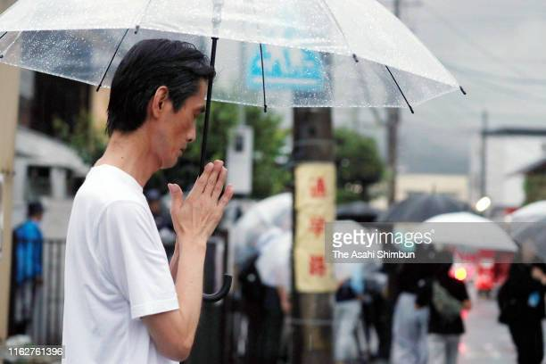 Man prays for the victims after an arson at a studio of Kyoto Animation Co. On July 18, 2019 in Kyoto, Japan. Police suspect an arsonist set a fire...