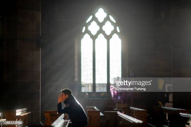 Man prays in a church as shoppers make their last minute purchases on Christmas Eve on December 24, 2018 in Birmingham, England. Financial management...
