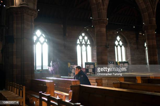 A man prays in a church as shoppers make their last minute purchases on Christmas Eve on December 24 2018 in Birmingham England Financial management...