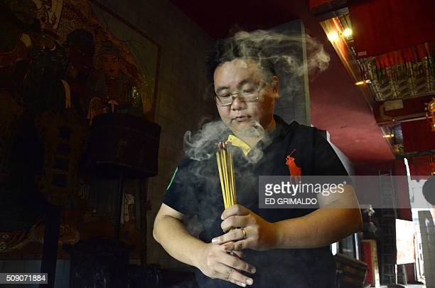 A man prays in Chinatown in Panama City on February 8 2016 This year the Chinese community celebrates the Year of the Monkey AFP PHOTO/ ED GRIMALDO /...