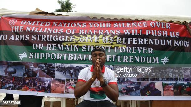 A man prays in front of a banner displayed on May 30 2018 at the Biafra district in Abidjan during a ceremony commemorating the Biafran War from 1967...