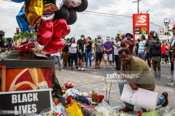 TOPSHOT A man prays in front of a makeshift memorial in honor of George Floyd who died in custody on May 26 2020 in Minneapolis Minnesota A video of...