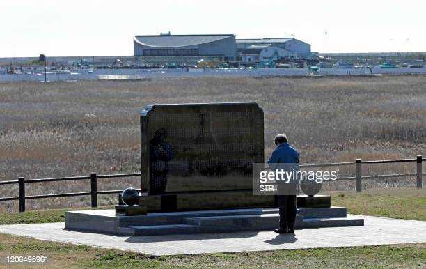 A man prays in front of a memorial monument in Namie Fukushima Prefecture on March 11 2020 on the ninth anniversary of the 2011 tsunami disaster...