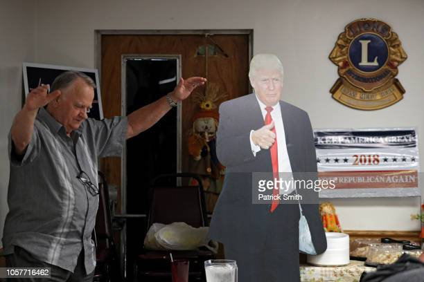 A man prays in front of a President Donald Trump cutout as West Virginia Republican Senate Candidate Patrick Morrisey campaigns ahead of midterm...